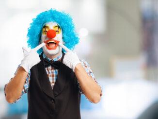 Klaun si drží prsty úsměv.