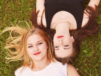 Blondýna a bruneta leží v trávě.