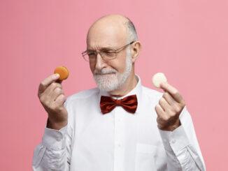 Starší muž drží v každé ruce jednu sušenku.