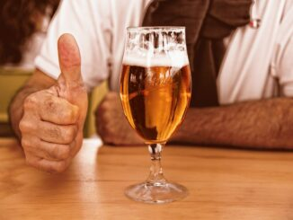 Detail piva, muž ukazuje palec nahoru.