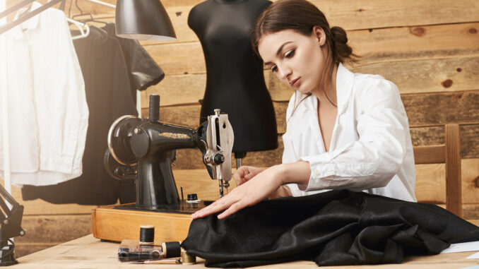 Žena šije na šicím stroji.