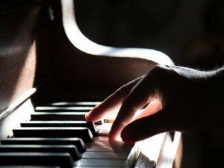 Detail ruky hrající na klavír.