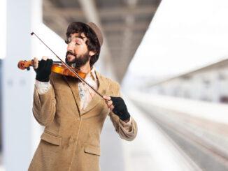 Šťastný žebrák hraje na housle.
