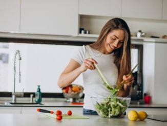 Žena s radostí připravuje salát.