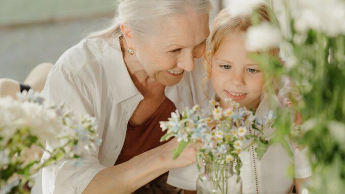 Babička ukazuje vnučce kytky.