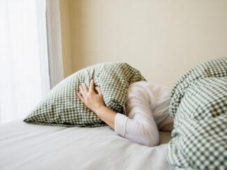Žena leží s hlavou pod polštářem.