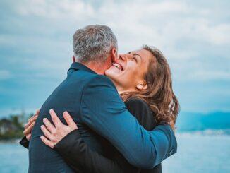 Muž a smějící se žena se objímají.