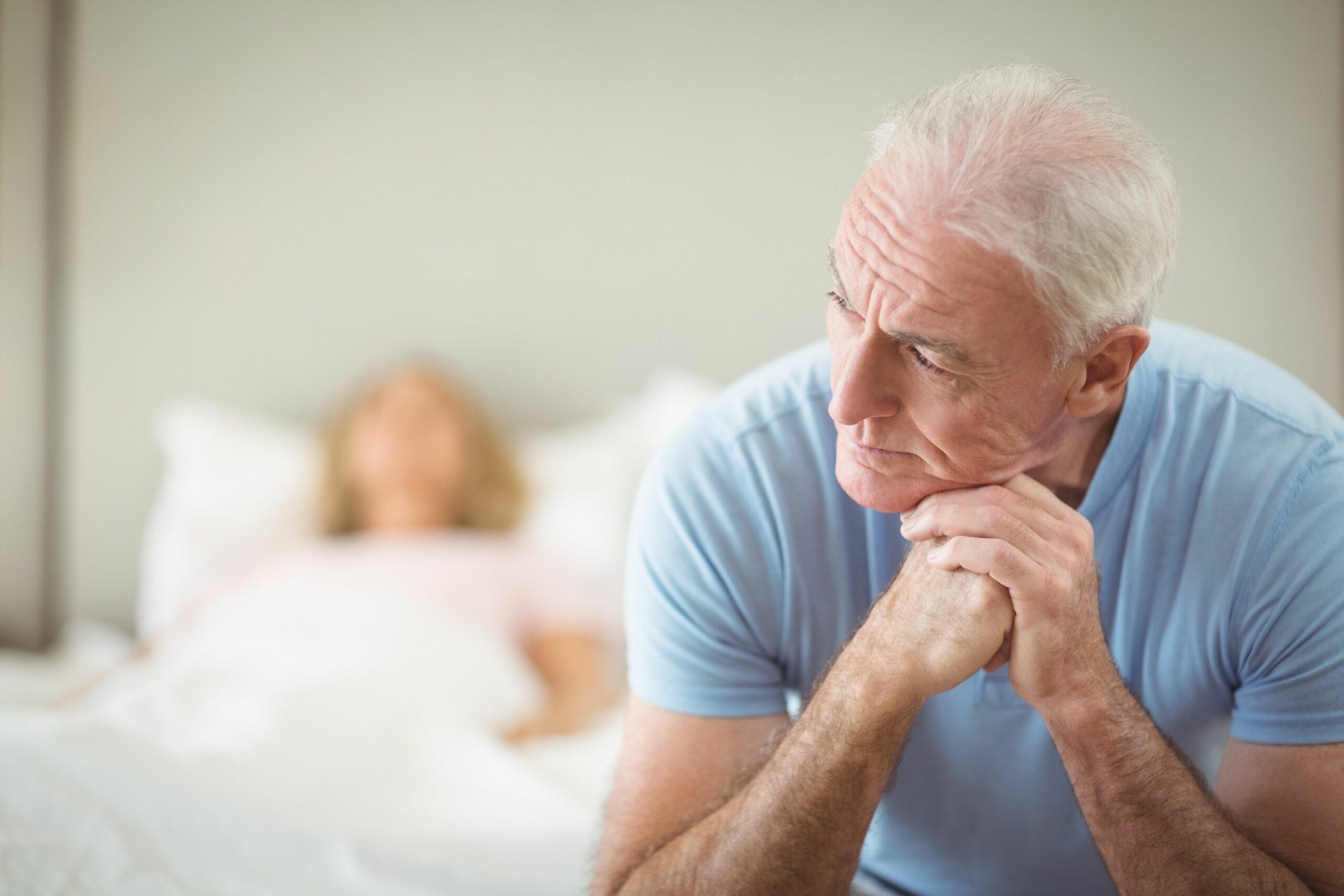 Starší muž sedí na posteli, v níž leží žena.