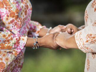 Dvě starší dámy se drží za ruce.
