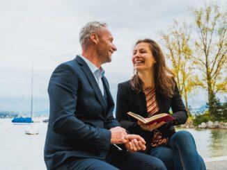 Dva lidé sedící na laviččce, žena čte knihu.