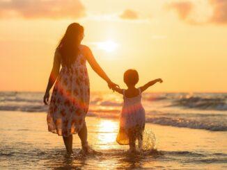 6ena s dítětem se prochází ruku v ruce po pláži