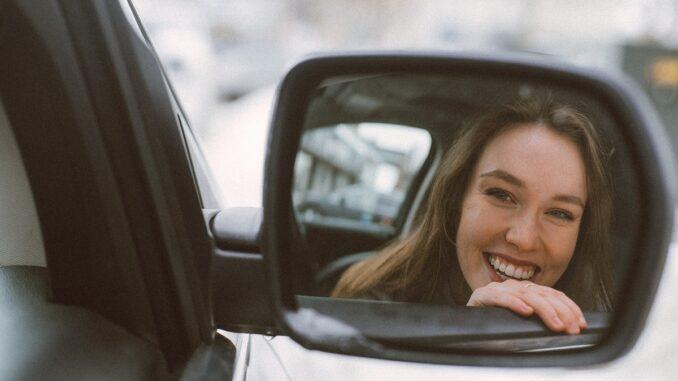 zrcadlo na autě ve kterém je vidět usměvavá žena.