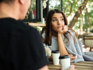 Zamyšlená žena sedí u kávy s mužem.
