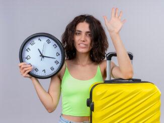Žena s kufrem a hodinami v ruce.