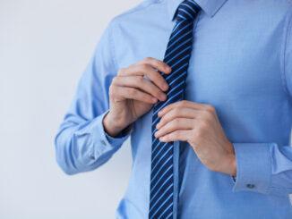 Muž si upravuje kravatu