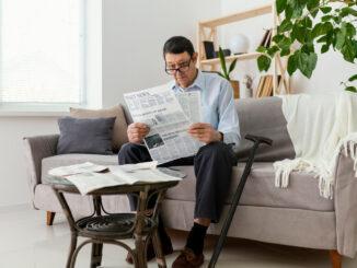 Muž na gauči si čte noviny.