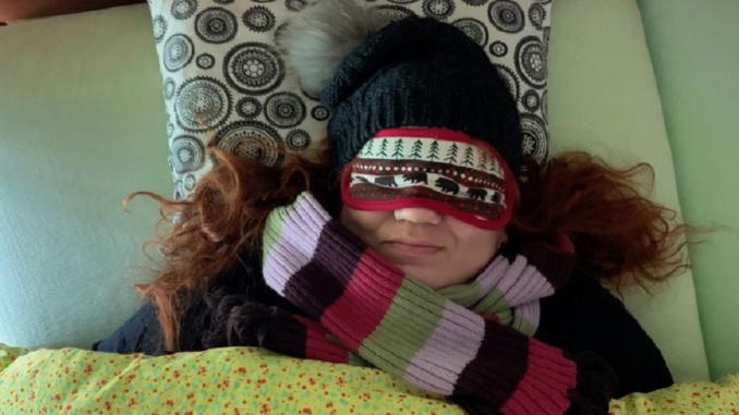 Paní v ložnici s čepicí na hlavě a pod peřinou