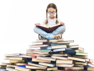 Dívka sedí na hromadě knih.