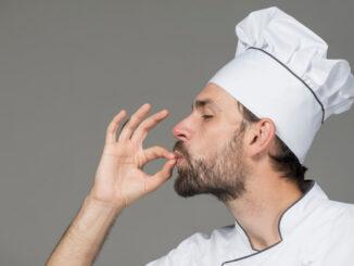 Muž v kuchařské čepici s gestem naznačujícím, že jídlo bylo vynikající.
