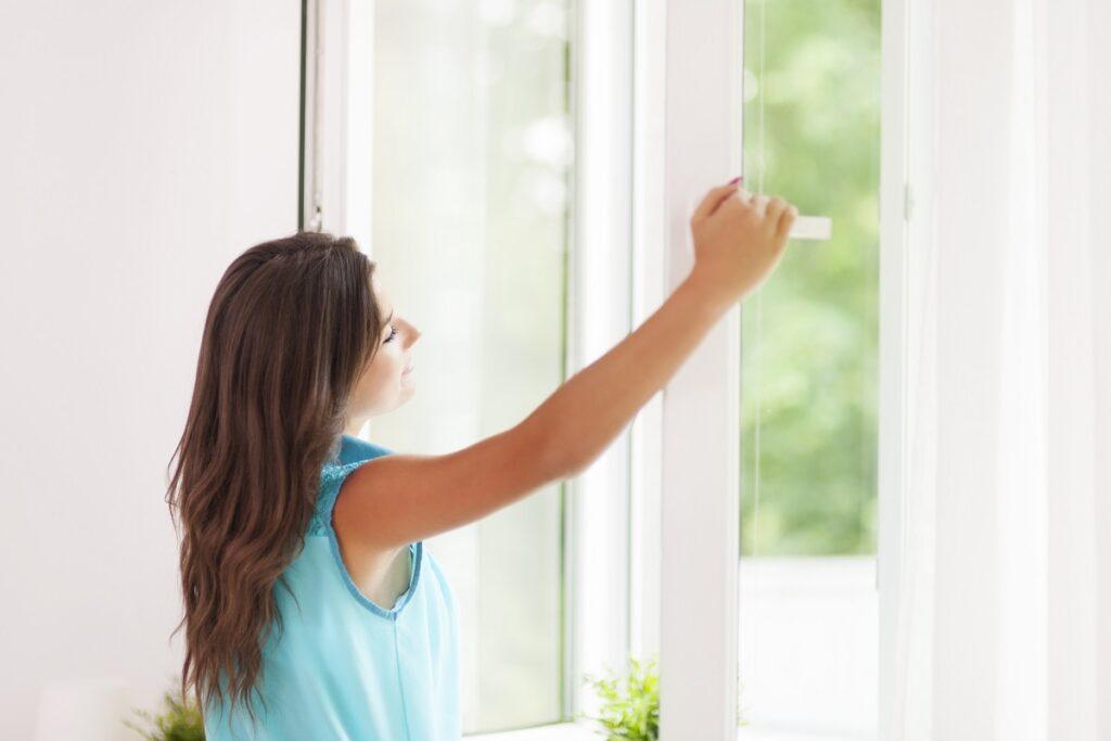 Žena otevírá okno.