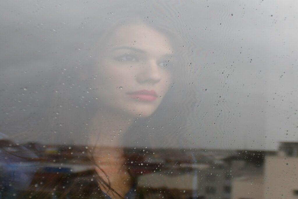 Žena se dívá z okna.