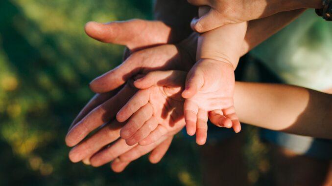 Detail rukou dítěte a dospělého.