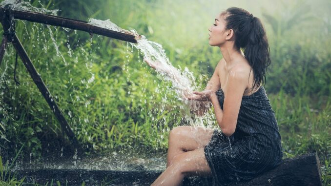 Žena se koupe v prameni.