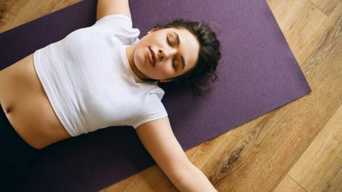 Žena leží na karimatce.