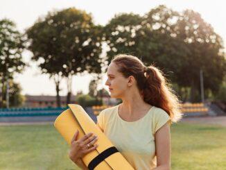 Mladá žena si nese podložku na cvičení.
