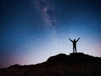 Silueta muže proti nočnímu nebi.