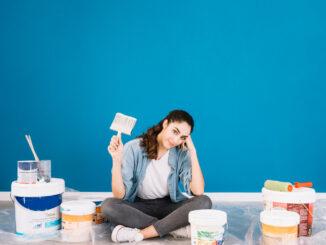 Žena sedí mezi barvami.