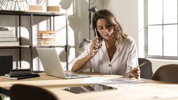 Žena za u notebooku telefonuje.