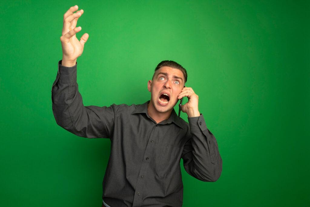Muž se rozčiluje do telefonu.